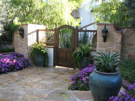 Spanish style stacked stone entry pillars with wrought